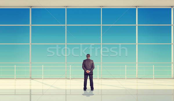 Businessman with hands behind in front of window Stock photo © cherezoff