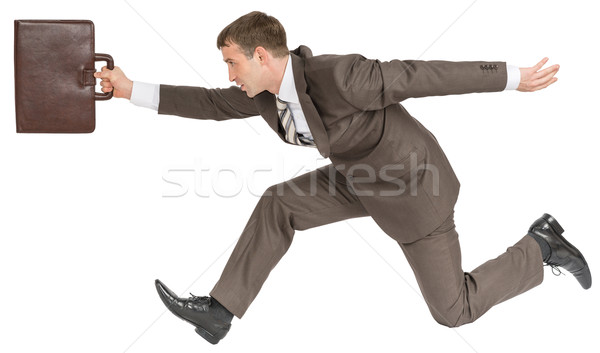 Businessman racing forward with suitcase Stock photo © cherezoff