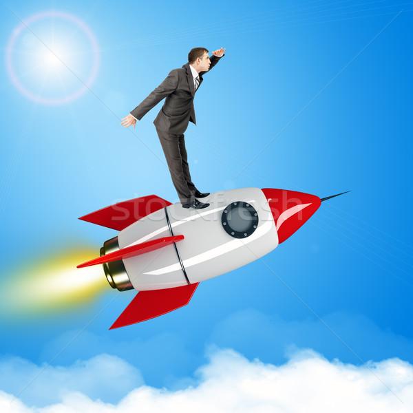 Businessman flying on jet rocket above city Stock photo © cherezoff