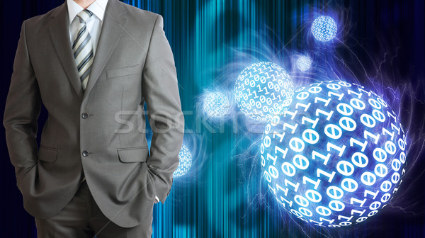 Businessman in a suit. Spheres of glowing digits Stock photo © cherezoff