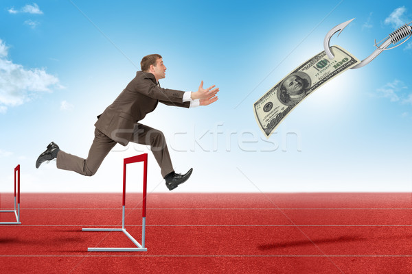 Man hopping over treadmill barrier with dollar  Stock photo © cherezoff