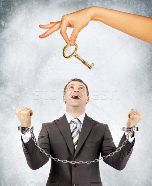 Businessman in handcuffs and big hand offering key Stock photo © cherezoff