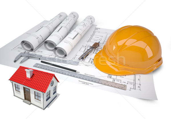 Small model house with red roof near architectural drawings and work tools Stock photo © cherezoff