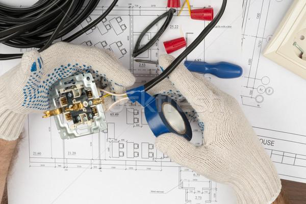 Man fixing socket with adhesive tape Stock photo © cherezoff