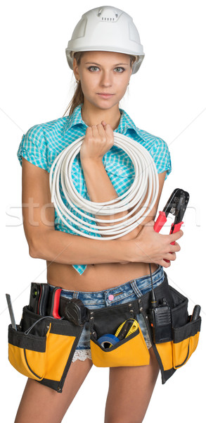 Pretty electrician in helmet, shorts, shirt, tool belt with tools holding an electric cable Stock photo © cherezoff