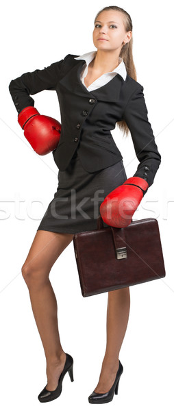 Businesswoman wearing boxing gloves standing akimbo Stock photo © cherezoff
