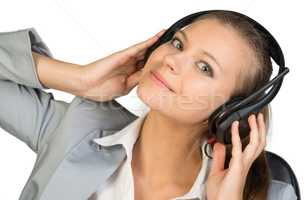 Businesswoman in headset with her hands on speakers Stock photo © cherezoff