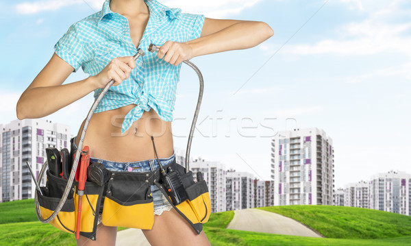 Woman holding two flexible hose. Cropped image. Green hills with road and buildings on background Stock photo © cherezoff