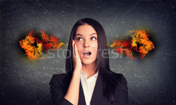 Surprised woman with fire from ears. Concrete gray wall as backdrop Stock photo © cherezoff