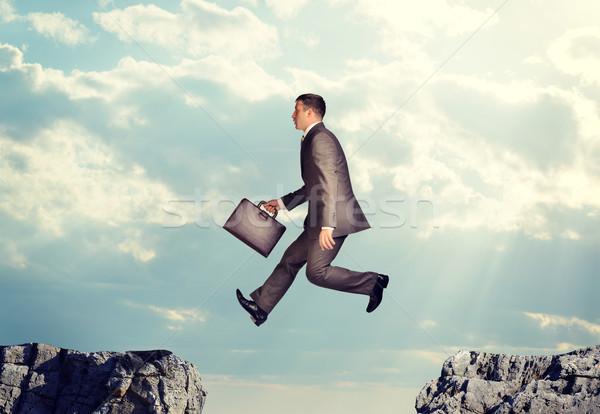 Stock photo: Businessman jumping over precipice