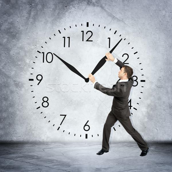 üzletember tart óramutató szürke fal óra Stock fotó © cherezoff
