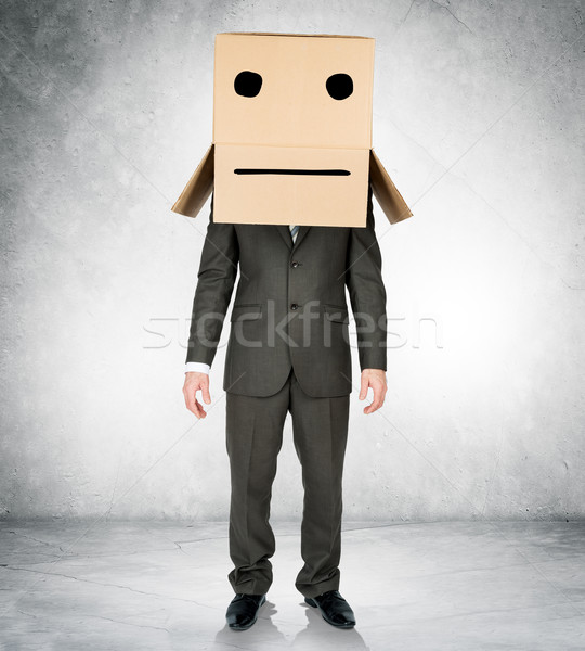 Businessman wearing carton box with drawn emotions Stock photo © cherezoff