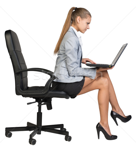 Businesswoman sitting on the edge of office chair, with laptop Stock photo © cherezoff