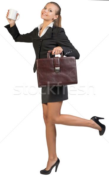 Businesswoman holding mug and briefcase  Stock photo © cherezoff
