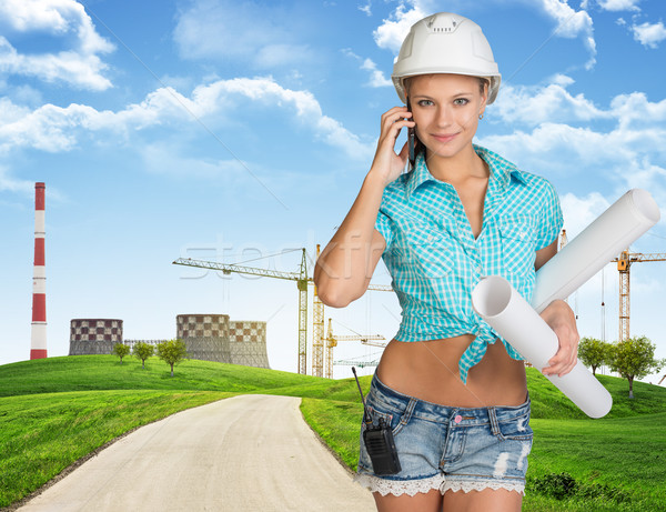 Woman in hard hat, holding drawing rolls calling on the phone Stock photo © cherezoff
