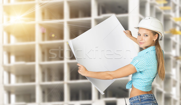 Woman holding blank drawing sheet in front of building under construction Stock photo © cherezoff
