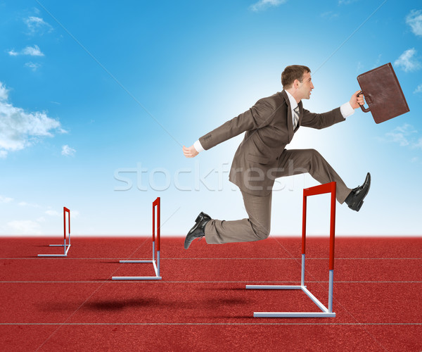 Businessman hopping over treadmill barrier Stock photo © cherezoff