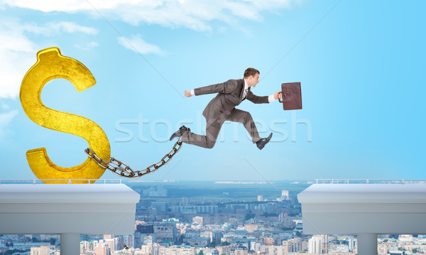 Stock photo: Man jumping over gap with gold dollar sign ballast