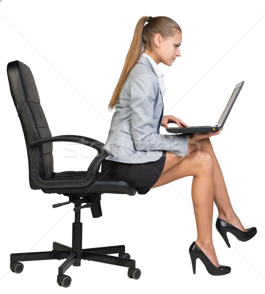 Femme d'affaires séance bord chaise de bureau portable regarder Photo stock © cherezoff