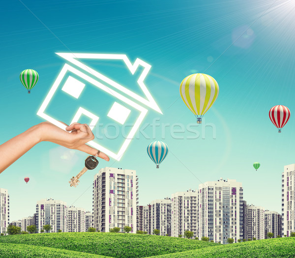 Female hand holding icon house and keys. Green hills with high-rise buildings as backdrop Stock photo © cherezoff