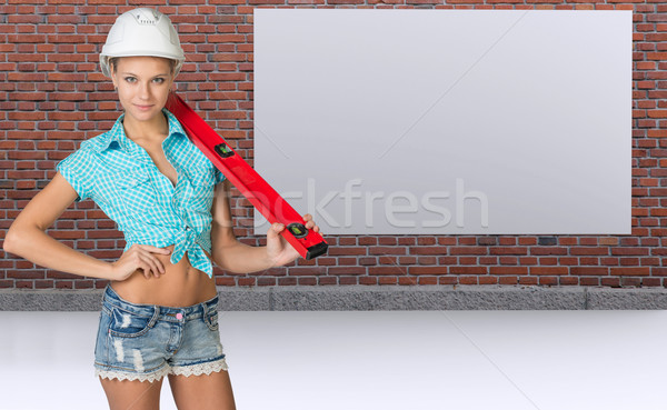 Woman in helmet holding spirit level, smiling. Brick wall and board as backdrop Stock photo © cherezoff