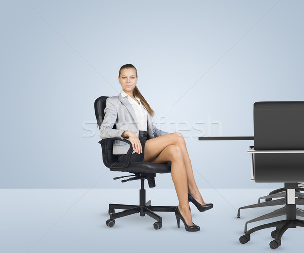 Businesslady sitting half-turned in chair with her crossed legs Stock photo © cherezoff