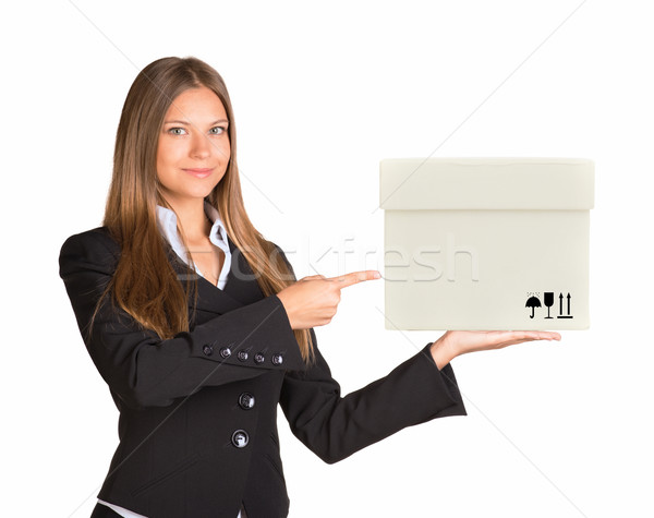 Businesslady holding and pointing at white box Stock photo © cherezoff