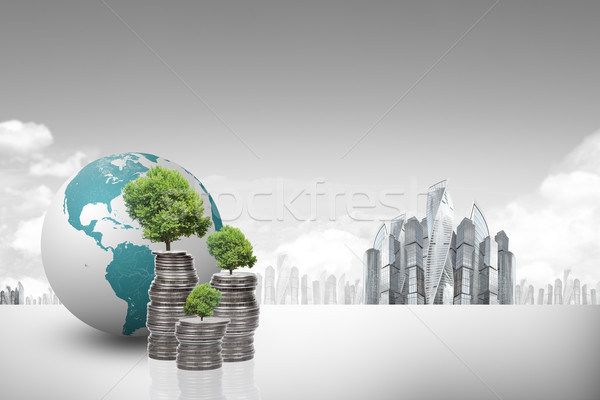 Earth globe with piles of coins Stock photo © cherezoff