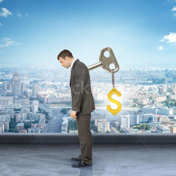 Empresario clave atrás signo de dólar mirando hacia abajo ciudad Foto stock © cherezoff