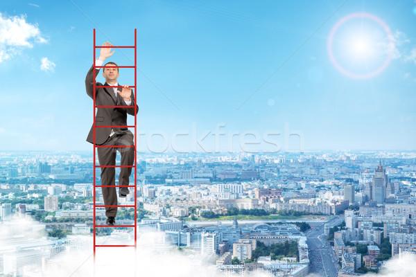 Businessman climbing red  ladder in sky Stock photo © cherezoff