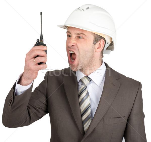 Businessman in helmet screaming at walkie-talkie Stock photo © cherezoff