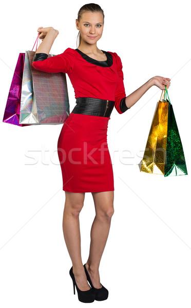 Half turned smiling woman handing bags up Stock photo © cherezoff
