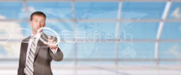 üzletember kisajtolás holografikus képernyő világtérkép égbolt Stock fotó © cherezoff