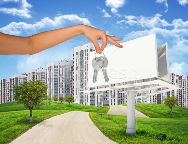 Stadsgezicht billboard arm sleutels blauwe hemel Stockfoto © cherezoff