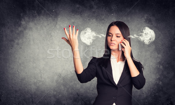 Expressive woman with steam from ears, talking on phone. Concrete gray as backdrop Stock photo © cherezoff
