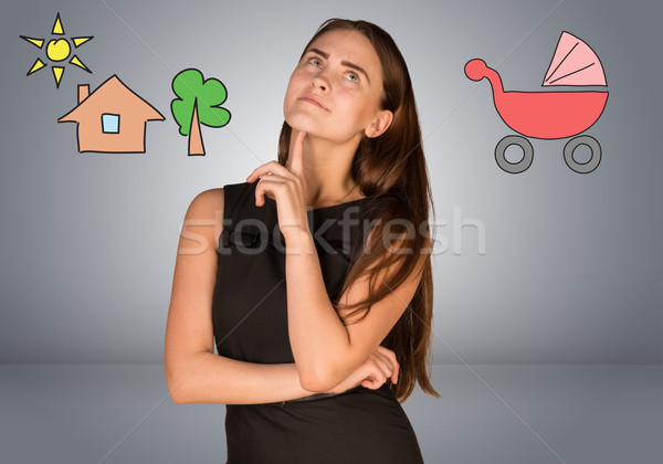 Business woman thinking over buggy and house with tree Stock photo © cherezoff