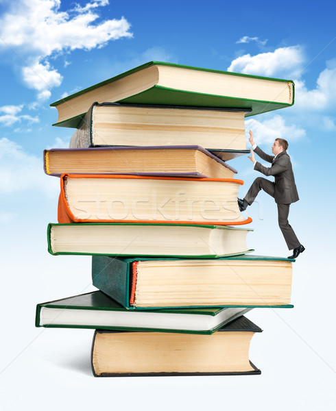 Pile of books with businessman climbing it Stock photo © cherezoff