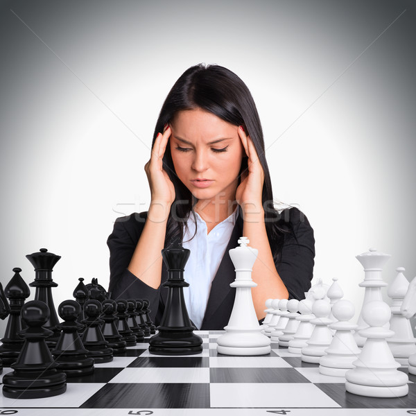 Lost in thought woman looking at chess board Stock photo © cherezoff