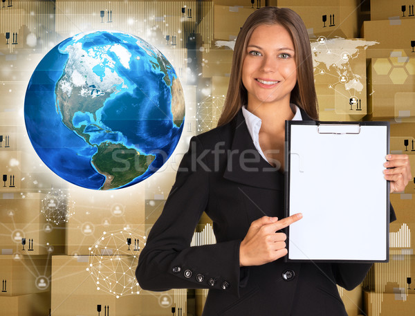 Businesswoman hold paper holder. Earth and wall of cardboard boxes Stock photo © cherezoff