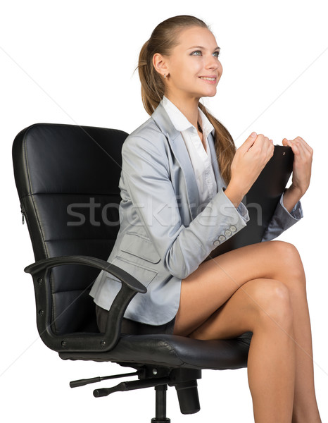 Businesswoman sitting on office chair with clipbord in hands, looking ahead, smiling Stock photo © cherezoff
