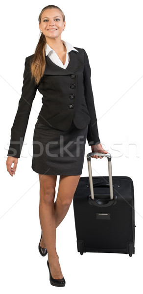 Businesswoman walking with wheeled suitcase, looking at camera, smiling Stock photo © cherezoff