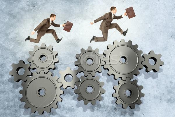 Two businessmen running on wheel gears Stock photo © cherezoff
