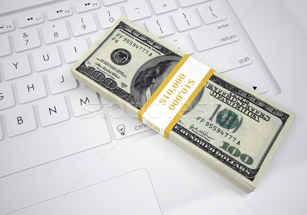 Bundle of dollar bills lying on computer keyboard Stock photo © cherezoff