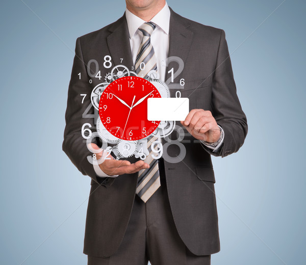 Man hold empty card and clockwork with flying figures Stock photo © cherezoff
