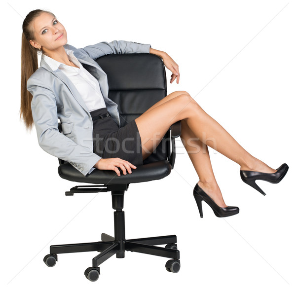 Businesswoman on office chair with her legs over armrest Stock photo © cherezoff