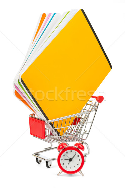 Shopping cart with copybooks and alarm clock Stock photo © cherezoff