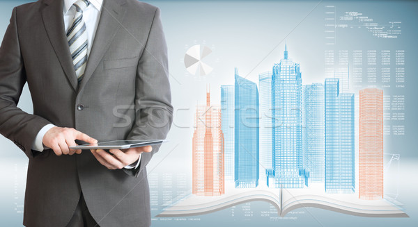 Businessman with tablet pc. High-tech skyscrapers Stock photo © cherezoff