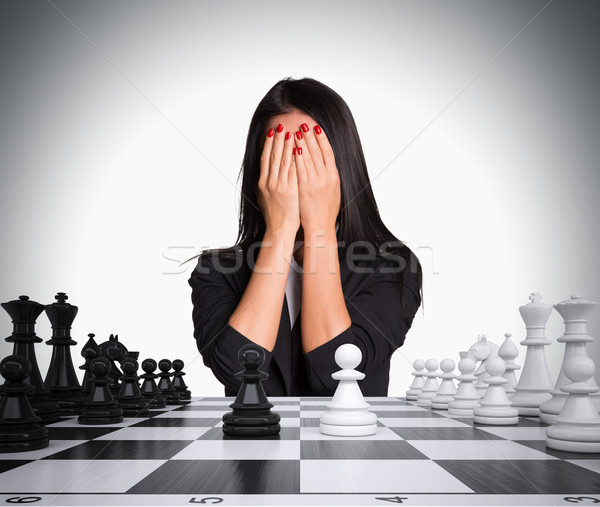 Businesswoman covering her face with hands. Chessboard and chess Stock photo © cherezoff