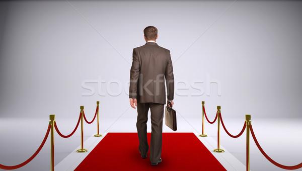 бизнесмен костюм портфель вперед красный ковер Сток-фото © cherezoff