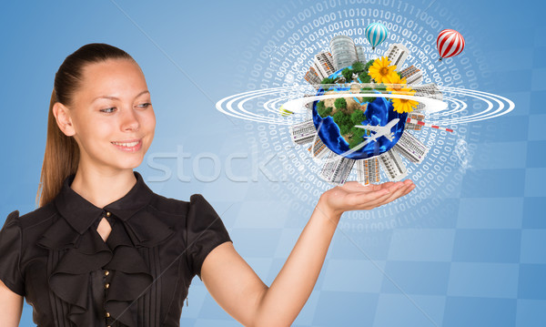 Beautiful businesswoman holding miniature Earth with trees, houses etc. on it Stock photo © cherezoff